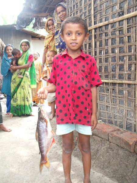 Boy holding a pangasius catfish (photograph by Ben Belton)