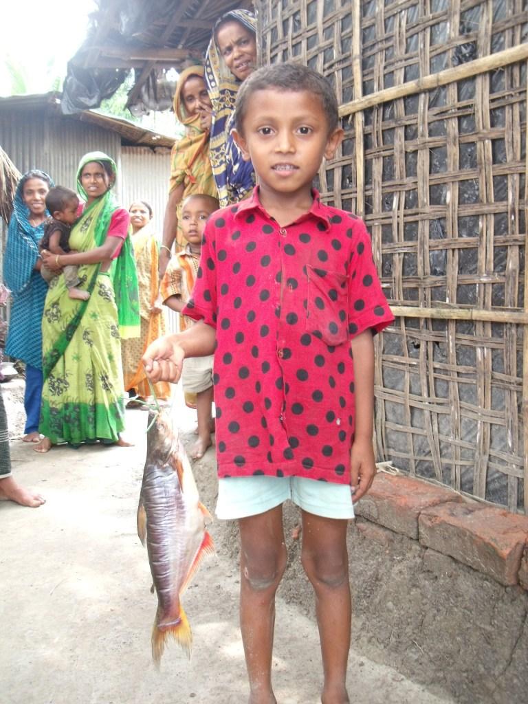Boy holding a pangasius catfish (photograph by Ben Belton)