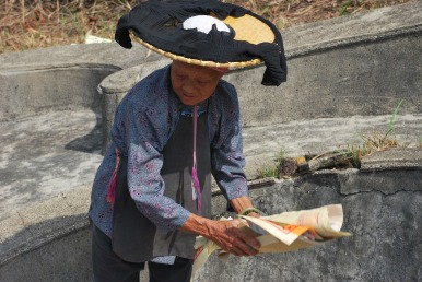 A walled village woman is getting the joss paper ready for burning as a way to worship their ancestors in the fall festival ritual