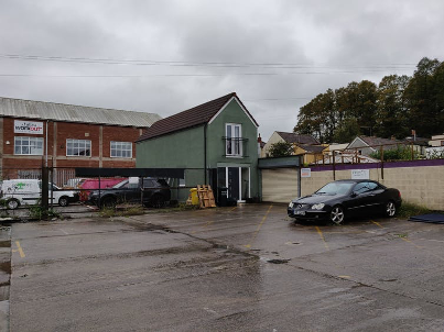 Car park and house under grey sky